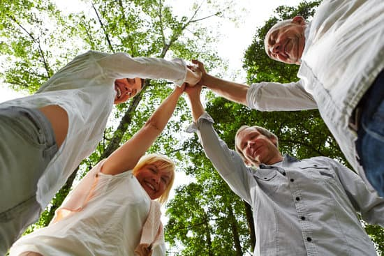 Happy team of seniors makes hight five in nature